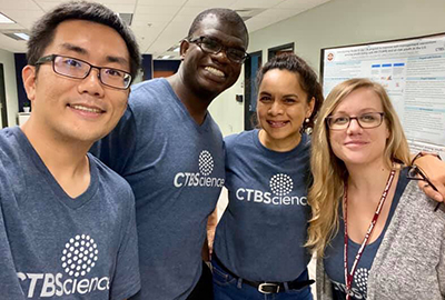 Four staff members in CTBScience t-shirts take a photo together.