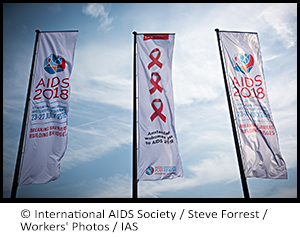 Photo of 3 flags at AIDS 2018 with the event logo